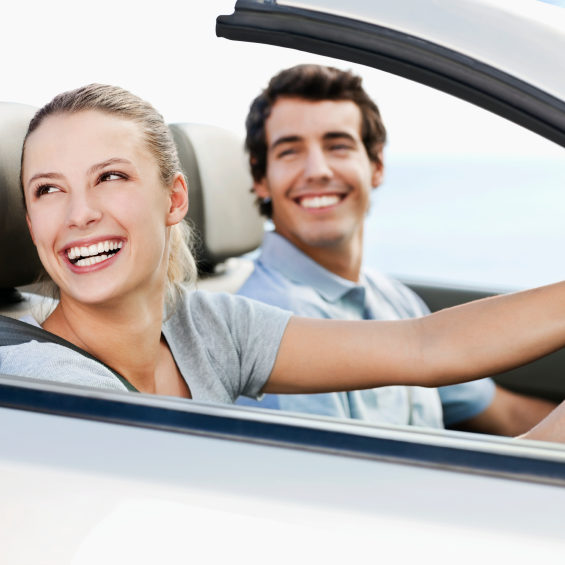 Young man and woman smile back over their shoulders while seated in a convertible car.  Horizontal shot.